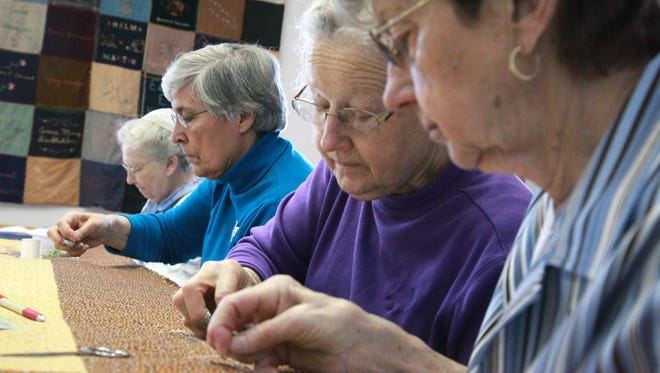 Springdale Mennonite Church sewing circle members, from left, Ruth Showalter, Edith Kuhns, Bertha Showalter and Alice Hostetler  work on a quilting project to donate to the Virginia Relief Sale, which raises hundreds of thousands of dollars each year for humanitarian aid. Generations of Springdale women have been quilting for relief work since 1935.