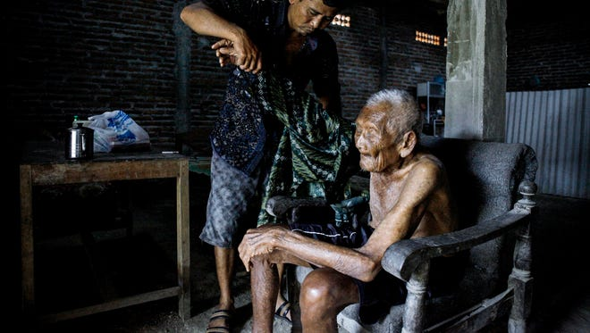 Sodimejo, also called Mbah Gotho, is shown with his grandson in Central Java, Indonesia, on Feb. 25, 2017.