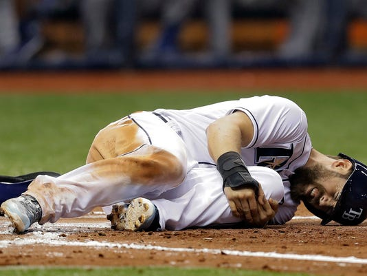 Tampa Bay Rays' Steven Souza Jr. grabs his knee after he was hurt sliding into Toronto Blue Jays catcher Russell Martin while trying to score on a fielder's choice by Tim Beckham during the fifth inning of a baseball game Thursday, April 6, 2017, in St. Petersburg, Fla. Souza Jr., was able to remain in the game. (AP Photo/Chris O'Meara)