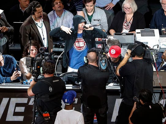 Eminem cheers the crowd before tipoff at the Detroit