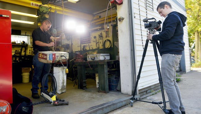 Derek Moul, left, a service technician at Hoist & Crane Repair in Manchester Township, demonstrates how to unload a hoist as Eric Hales of 617 Production Group records it .