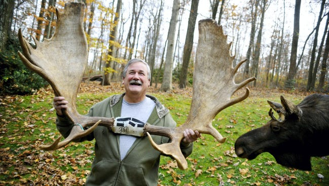 Jack Hoffman, 60, of Spring Garden Township, stands for a portrait Nov. 15. He holds up the rack of a moose he shot in Alaska in September 2012. To the right is a moose cape that a friend sent him and to which taxidermist Steve Prowell affixed Hoffman's moose rack.