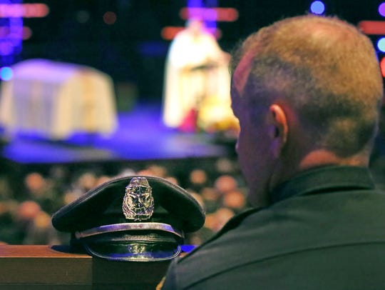 Colleagues listen to stories about Dallas police Officer