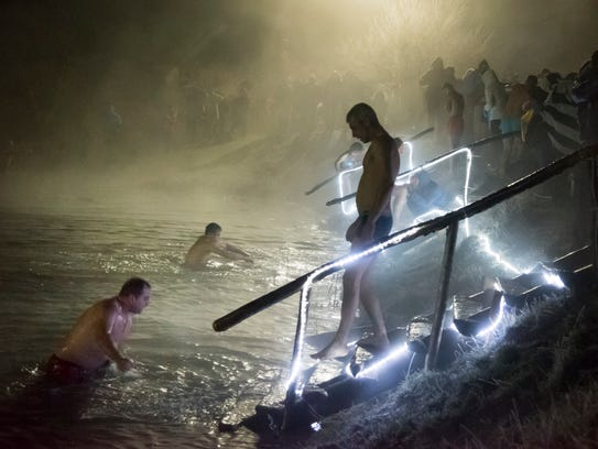 Russian Orthodox believers bathe in ice water in a