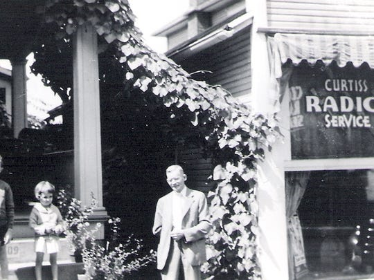 An unknown man and children stand between 309 and 311 N. Broad St. in this 1936 photo. Curtiss Radio Service was at 311 N. Broad after North End Press moved into 315.