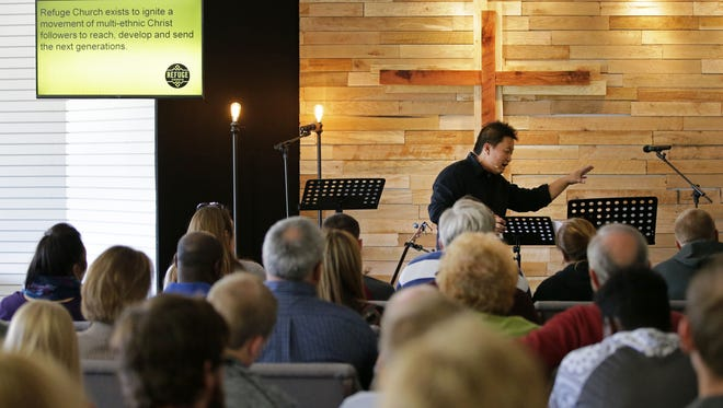 Bee Vang leads a morning service as the Refuge church holds its first service at its new location on Wisconsin Avenue on Sunday, October 9, 2016 in Appleton, Wisconsin. The multiethnic church includes refugees as part of its congregation.