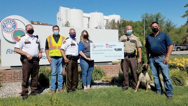 Pictured left to right: Chief Deputy Mike Norland, Ryan Wall (American Crystal Sugar factory manager), Sheriff Jim Tadman, Tammy Moe (American Crystal Sugar factory accountant), K9 Handler Deputy Kyle Olson, K9 Deputy Buffy, and Eric Ptacek (American Crystal Sugar agronomy manager).