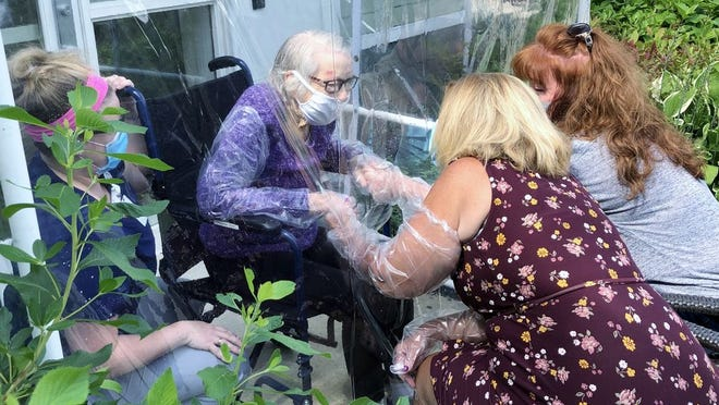 Protected by plastic, Amy Dooley, right, of Abington, and Cindy Walsh, center, of Rockland, visit their 91-year-old mother, Evelyn MacDonald, outside at The Dwyer Home at Fairing Way in Union Point in Weymouth.