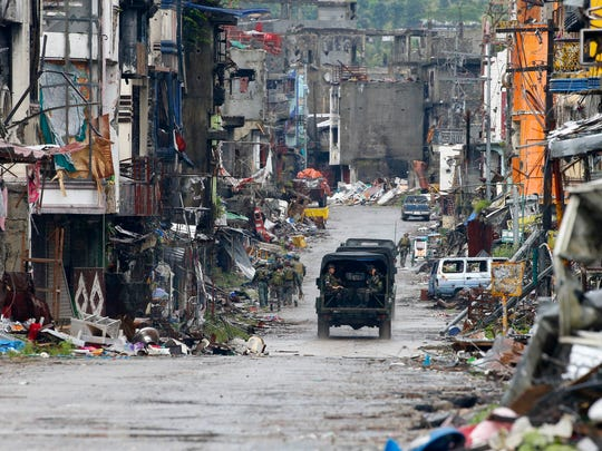 In this October photo, troops patrol the decimated streets of Marawi city, just 159 miles from where John Venditti spent a week on a surgical mission in September.