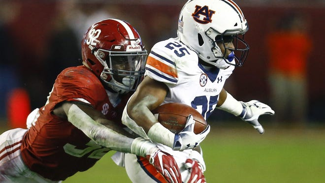 In this Nov. 24, 2018, file photo, Auburn running back Shaun Shivers (25) is tackled by Alabama linebacker Dylan Moses (32) during the second half of an NCAA college football game in Tuscaloosa, Ala. The Tide opens next Saturday at Missouri with Moses returning when he might otherwise have left for the NFL.