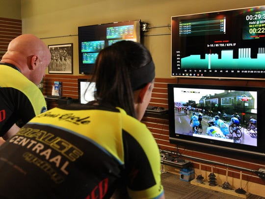 Cyclists ride on indoor trainers connected to the internet