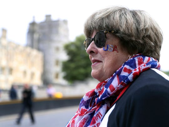 American royal fan Donna Werner, and who has come over to Britain specially for the upcoming royal wedding of Britain's Prince Harry and Meghan Markle, shows off her placards in her position along the carriage route in Windsor, England, Wednesday, May 16, 2018.