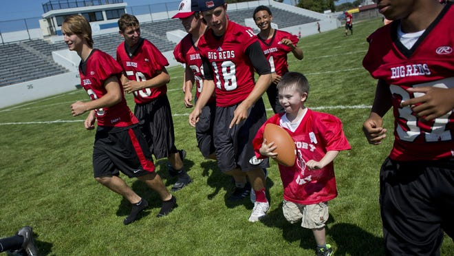 Bryson Coronado runs the ball to the end zone as players run along side and make blocks during Victory Day Saturday, August 15, 2015 in Memorial Stadium at Port Huron High School. The event paired special needs students with mentors from the football and cheerleading teams.