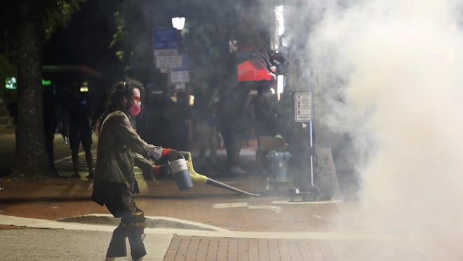 A protester uses a leaf blower to ward off tear gas as Athens-Clarke County police officers move in on demonstrators in downtown Athens last Sunday.
