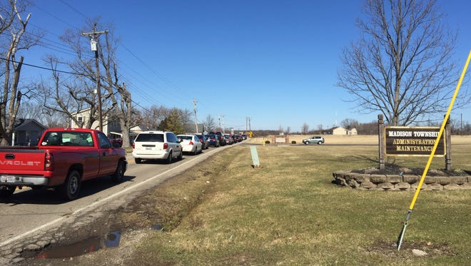 Cars wait along Alexandria Road to pick up students after a shooting at Madison High School three years ago.