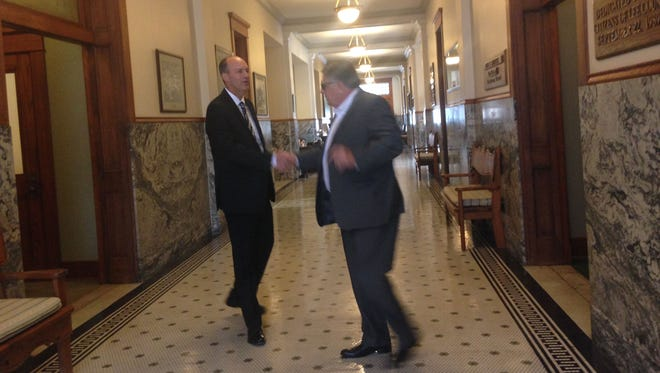 Lee County airports chief Bob Ball, right, shakes hands with Jeff Mulder before leaving the  county Old Courthouse on Tuesday. Mulder, who currently is director of airports for Tulsa, Oklahoma,  is Lee County commissioners' first choice for succeeding Ball, who is retiring. Contract negotiations are the next step in the hiring process.