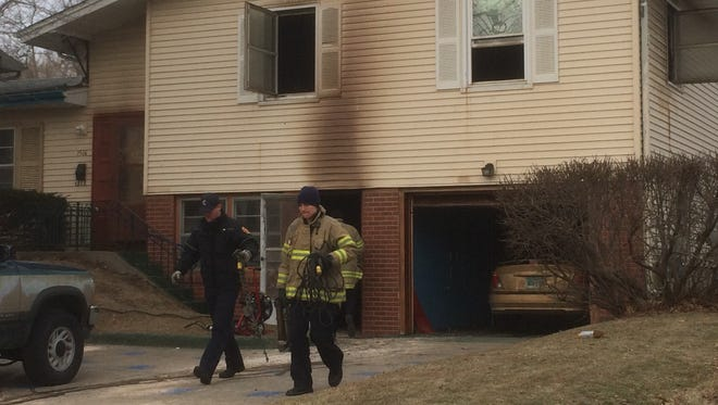 Iowa City Fire Department personnel walk in front of a house at 1516 Rochester Ave. Sunday, where an early morning fire killed one person.