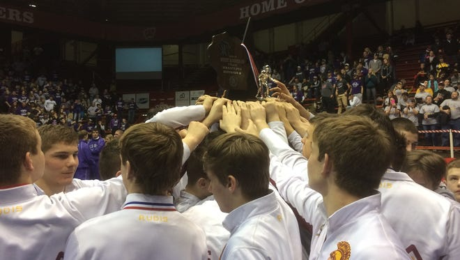 The Luxemburg-Casco wrestling team raises the WIAA Division 2 state runner-up trophy after falling to Ellsworth 27-26 in the championship dual on Saturday at the UW Field House in Madison.