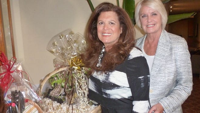 Friends of Hidden Harvest president Dee Brown and vice president Eileen Hall standing near one of many raffle baskets