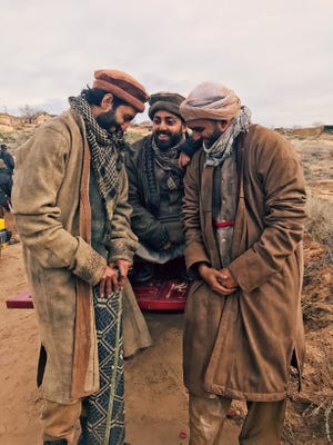 """Burrell College of Osteopathic Medicine student Haris, Humza, and Harris Ahmed talk between takes on the set of """"Horse Soldiers,"""" which is being filmed in New Mexico."""