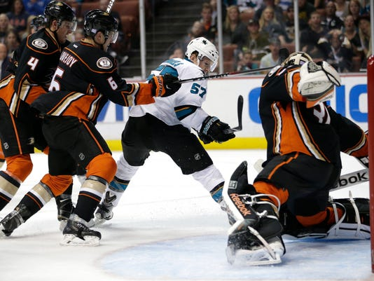 San Jose Sharks' Tommy Wingels, center, tries to score against Anaheim Ducks goalie Frederik Andersen, right, of Denmark, as he is defended by Anaheim Ducks' Cam Fowler, left, and Ben Lovejoy during the first period of an NHL hockey game Sunday, Oct. 26, 2014, in Anaheim, Calif. (AP Photo/Jae C. Hong)