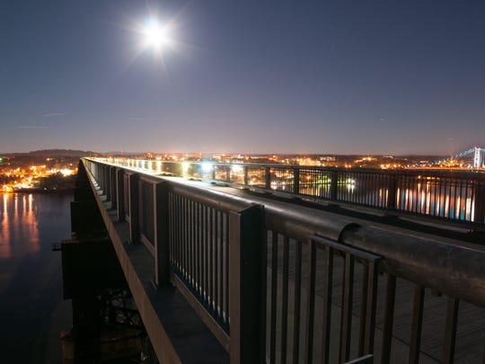 Beyond the Walkway Over the Hudson State Historic Park, lights from Poughkeepsie brighten the night sky.