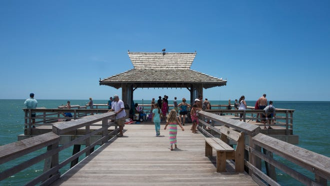 Tourists and locals take in the Gulf of Mexico from the Naples Pier on August 11, 2016 in Naples.