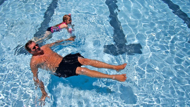 Paul Lehrman and his daughter Jessie Lehrman swim together May 30, 2015, at the Brookside Pool in Farmington.