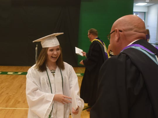 A Yellville-Summit senior laughs as she approaches Superintendent Wes Henderson on Friday night. The graduate almost left her diploma with high school principal David Wyatt.
