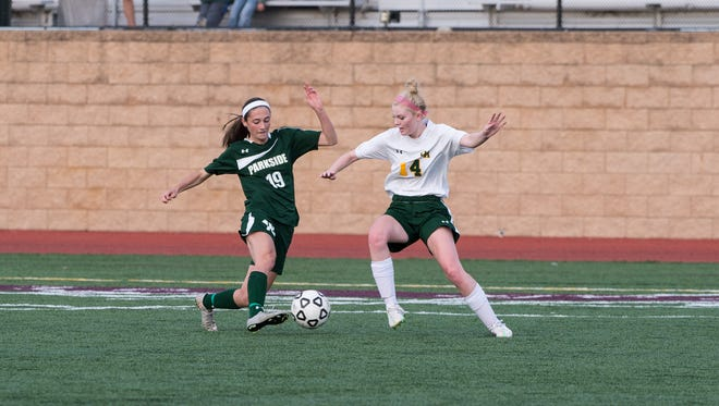 Parkside's Blair Vilov (19) attempts to move the ball around Queen Anne's Meagan Lukehart (14).
