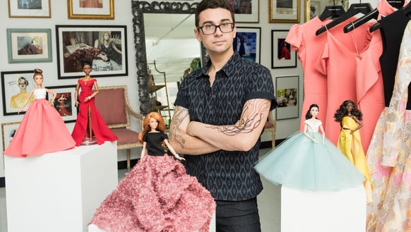 Christian Siriano poses with the fashion Barbies he