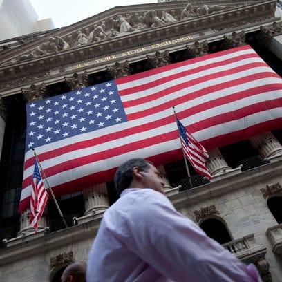 A pedestrian walks past the New York Stock Exchange