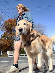 Audrey Stone walks with her guide dog Figo along Main