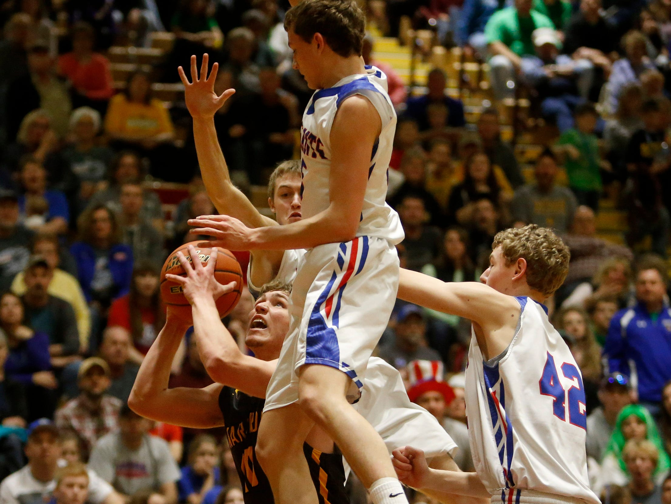 Wolsey-Wessington's Darin Tschetter, left, looks for a clear shot under the basket as Parker's Shane Kasten, front center, Chayse McKenney, back center and Camden Bialas, right, defend during Friday's semi-final game at the South Dakota Class B Boys Basketball Tournament at Wachs Arena. American News Photo by John Davis taken 3/17/2017