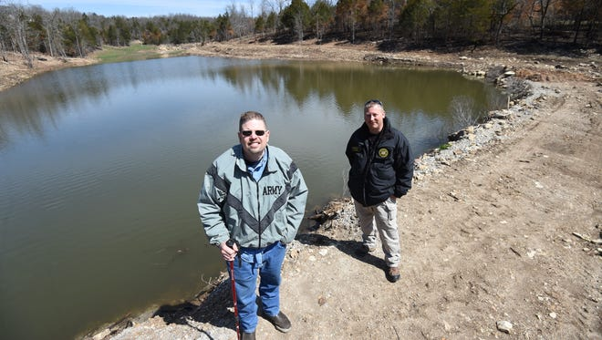 Eldon Cooper, right, and Sgt. Lee Sanders stand next to Cooper's pond at the spot where he rolled the tractor on Feb. 28., 2018, Sanders and others helped rescue the Clarkridge man.