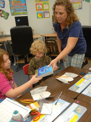 Amy Rouskey, a member of the Rotary Club of Cape Coral, hands out dictionaries to third-graders in 2010 at Pelican Elementary School.