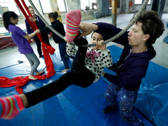 Helen Vazquez, center, learns an acrobatic move on a hanging ring during a workshop at the Trenton Circus Squad.