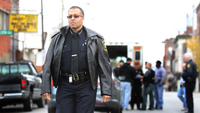 Cincinnati Police Chief James Craig walks down the street after over seeing District Four offices and SWAT round up gang members from the Walnut Hills Posse gang Friday in the 700 block of McMillian October 28, 2011 in Walnut Hills.