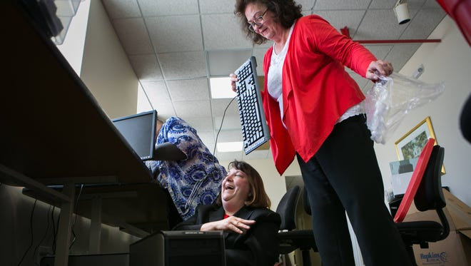 Holly Baker Maddams (center), executive director at Girls Inc. of Delaware gets help from office manager Linda Clark (right) and programs & training coordinator Dianne Vickery (left) as they set up computers in the computer lab area of their new Girls Inc. location at North Walnut Street, which will have its grand opening this weekend.