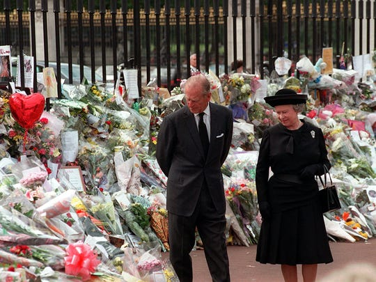 Queen Elizabeth II and Prince Philip look at tributes