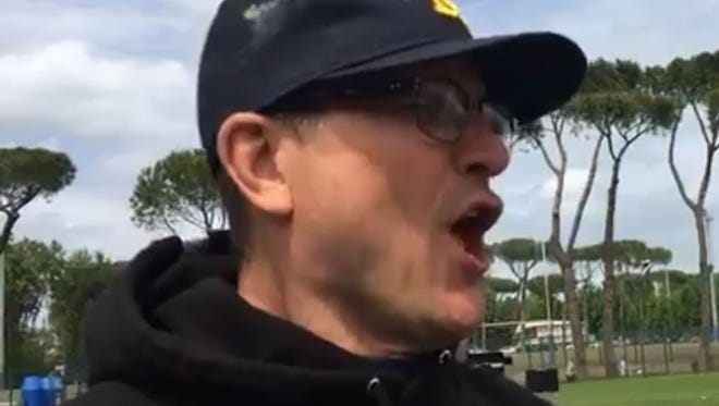 Michigan football coach Jim Harbaugh sings while meeting with the media after day two of practice in Rome for the Wolverines.