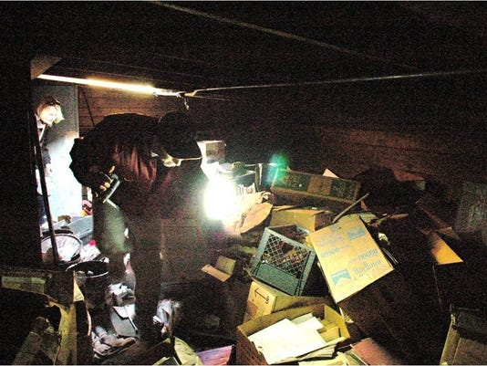 Ian Garbarine examines boxes of records in attic of St. Luke Building
