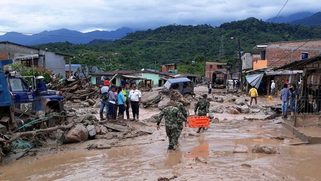 Soldiers and inhabitants proceed with rescue operations at the scene of a landslide in Mocoa, province of Putumayo, Colombia, on April 1, 2017.