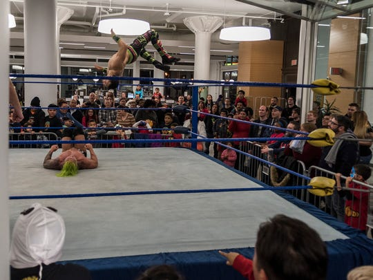 Professional wrestlers turn expectations on their head (literally) at the Mitchell Street branch of the Milwaukee Public Library.