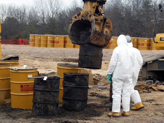 Workers remove drums of waste from an unlined landfill