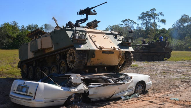 An Abbot FV432 armored personnel carrier crushes a Cadillac DeVille last November at Tank America in Melbourne.
