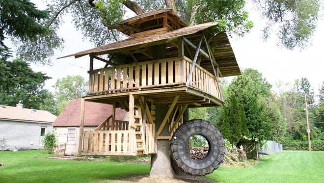 Travis Mead made a three-level treehouse out of recycled wood and a used tire for his daughter Lydia and newborn son Oliver.