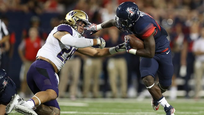 Running back J.J. Taylor #23 of the Wildcats rushes the football against the Huskies during the first quarter at Arizona Stadium on September 24, 2016 in Tucson, Arizona.