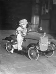 CIRCA 1920s:  Girl in toy pedal car with dog sitting