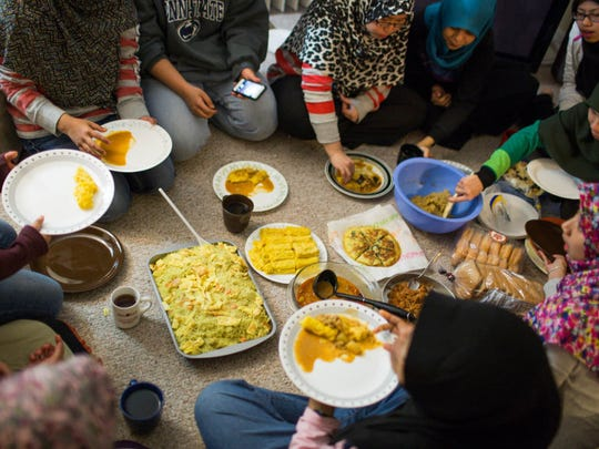 After a full day of fasting, the women gather around dishes of traditional Malaysian food, Rochester N.Y., May 8, 2014. (Photo by Kelly Jo Smart)